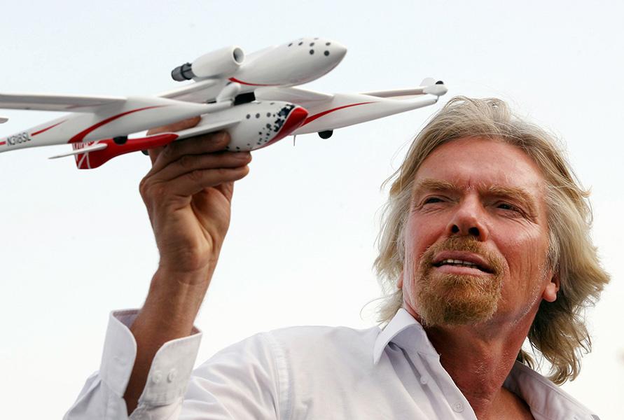 Foto do empresário Richard Branson segurando um protótipo de avião