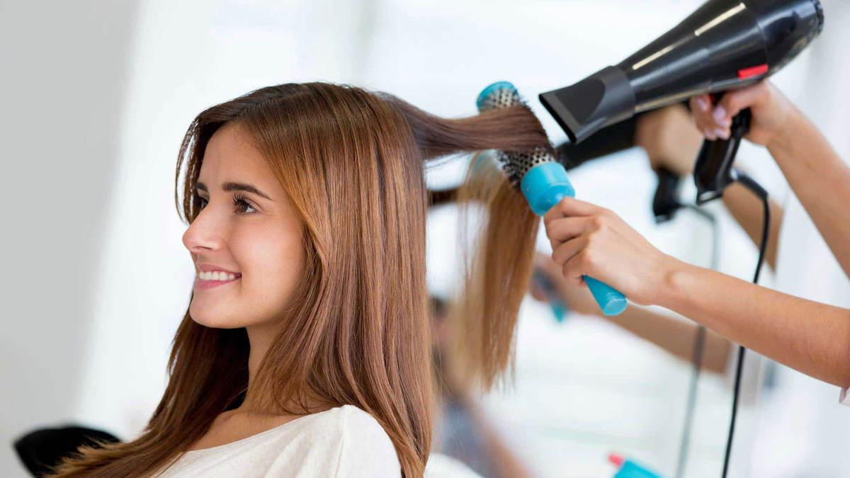 Mulher secando o cabelo de outra em salão de beleza, representando uma das tendências de franquias
