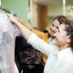 Foto de uma mulher escolhendo em uma loja de vestidos com a vendedora ao seu lado, representando vender melhor