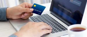 Foto de uma pessoa digitando em um notebook com um cartão em mãos, representando o que é certificado digital