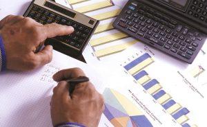 Foto de uma mão masculina digitando em uma calculadora e anotando em um papel, representando a contabilidade em são paulo