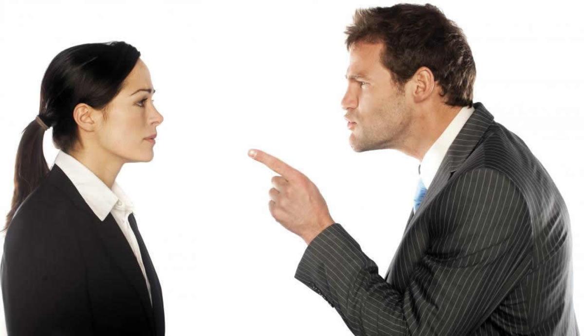 Foto de um homem apontando para uma mulher, representando a diferença entre líder e chefe