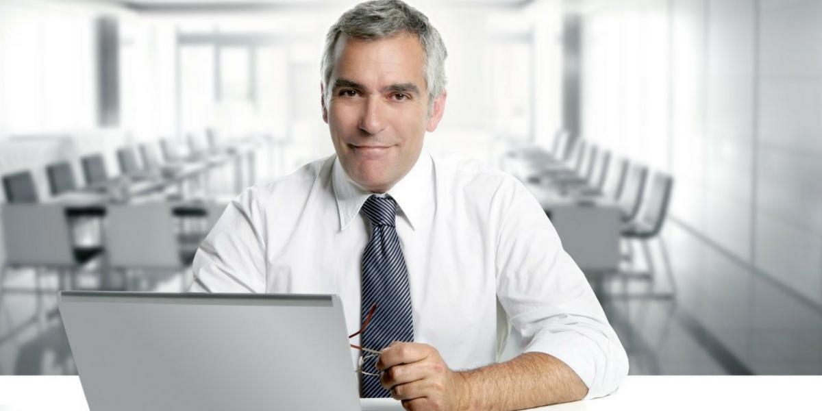 Foto de um homem sentado a uma mesa mexendo no computador, representando abrir mei pela internet