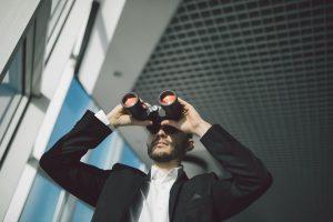 Empresário olhando em um binóculos, representando as ferramentas para monitorar os concorrentes