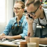 Foto de um casal, a mulher mexendo no computador e o rapaz falando ao telefone, representando transformar hobby em negócio