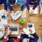 Foto de muitas pessoas sentadas à uma mesa, discutindo o marketing contábil