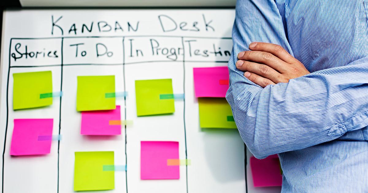 Foto de um homem em frente a um quadro kanban para gestão de produção nas empresas