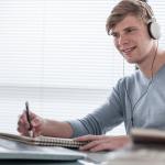 Rapaz mexendo no computador trabalhando e ouvindo música no trabalho