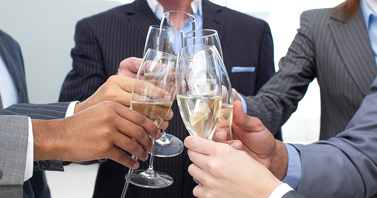 Foto de alguns empresários fazendo um brinde com champanhe, representando o início de 2018 sem dívidas
