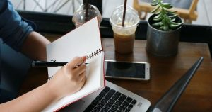 Pessoa com notebook, caderno e celular, representando empreender em Campinas - Abertura Simples