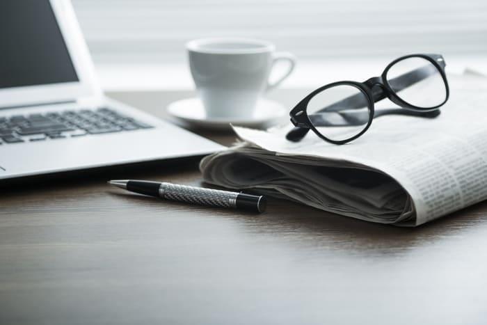 Notebook, jornal, óculos, caneta e xícara de café. representando empreender em São Paulo - Abertura Simples