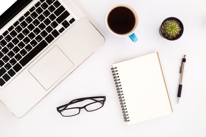 Notebook, óculos, caderno, xícara e caneta, representando empreender em Vila Velha - Abertura Simples