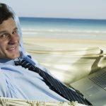 Foto de um empresário na praia com um notebook no colo, representando as férias de final de ano para empreendedores