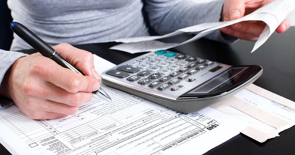 Foto de uma mulher fazendo contas dos impostos federais, estaduais e municipais