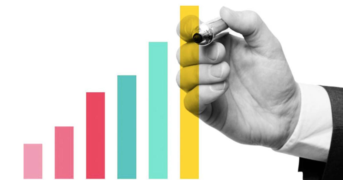 Foto da mão de um homem preenchendo gráficos, representando os indicadores de produtividade