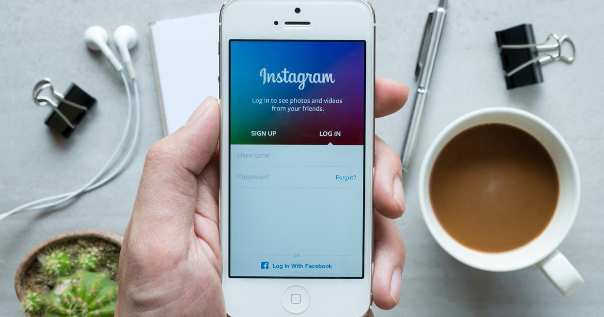 Foto de um celular com o aplicativo aberto e alguns elementos sobre uma mesa, representando o Instagram para empresas
