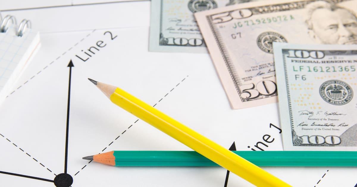 Lápis e notas de dinheiro, representando mudanças do simples nacional - Abertura Simples