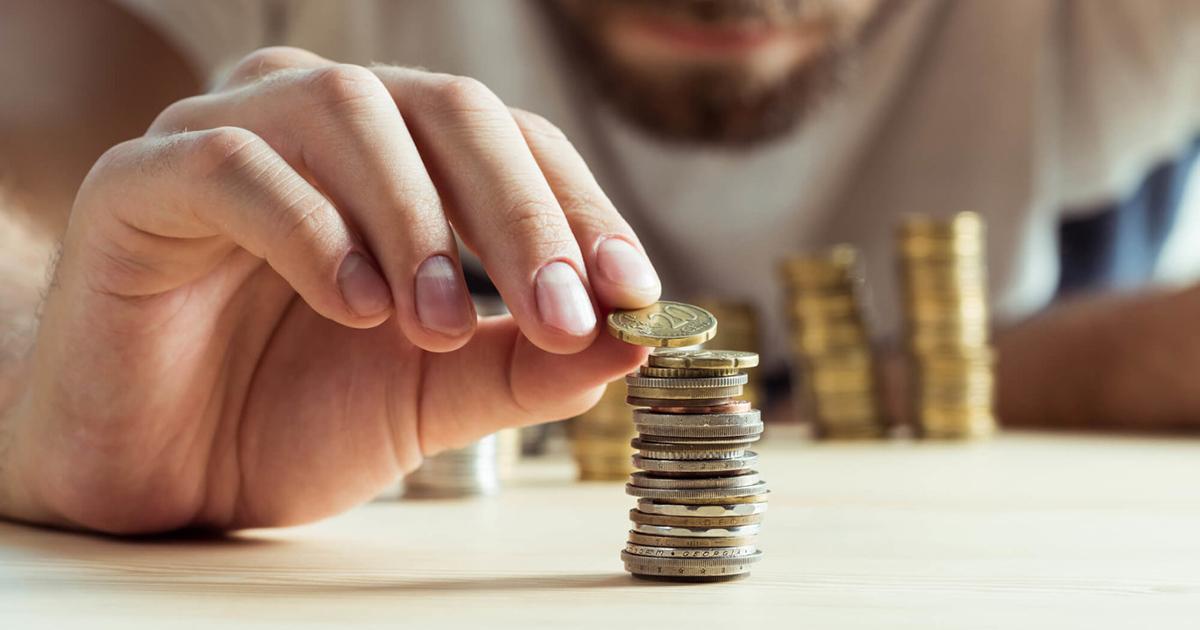 Foto de um homem contando moedas, representando o pequeno salário