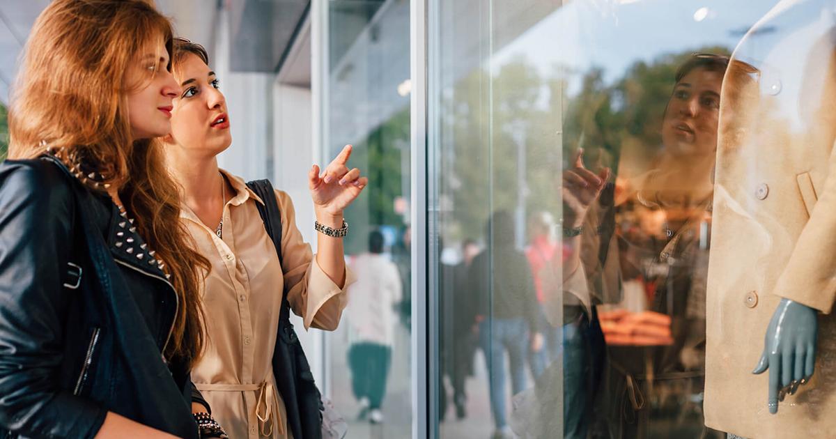 Foto de duas mulheres observando a vitrine de uma loja, representando as dicas para deixar o ponto de venda mais atraente