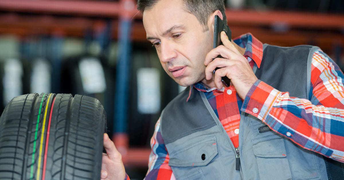 Homem olhando para um pneu, representando abrir uma borracharia - Abertura Simples