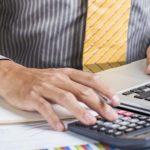 Foto de um homem com calculadora fazendo contas do Difal