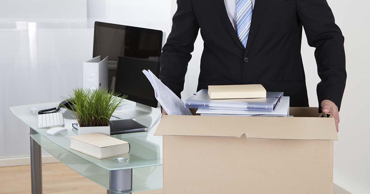 Foto de um homem carregando uma caixa com coisas de escritório representando as dicas para dispensar um funcionário