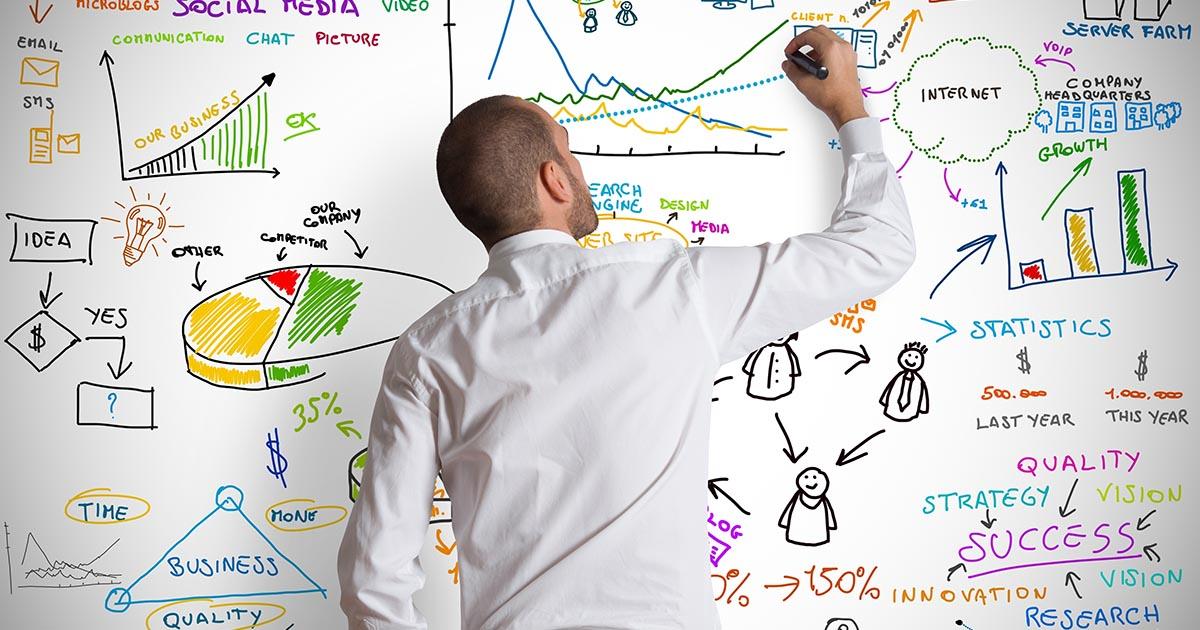 Foto de um homem anotando gráficos e anotações em uma lousa branca, representando a estratégia financeira para 2018