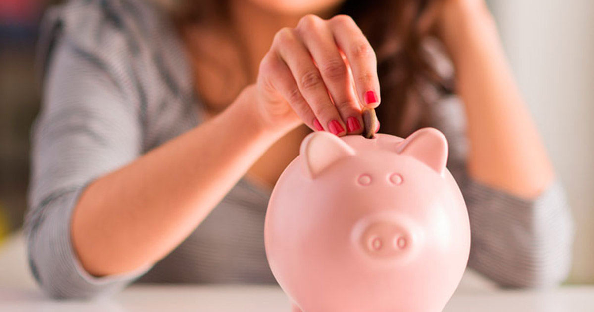 Foto de uma mulher colocando uma moeda em um cofre de porquinho, representando as finanças em dia