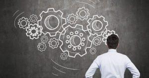 Foto de um homem de costas, observando um quadro negro com algumas engrenagens desenhadas, representando a inovação do seu negócio