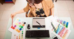 Foto e uma mulher designer, consultando uma paleta de cores, representando a criação de um logotipo