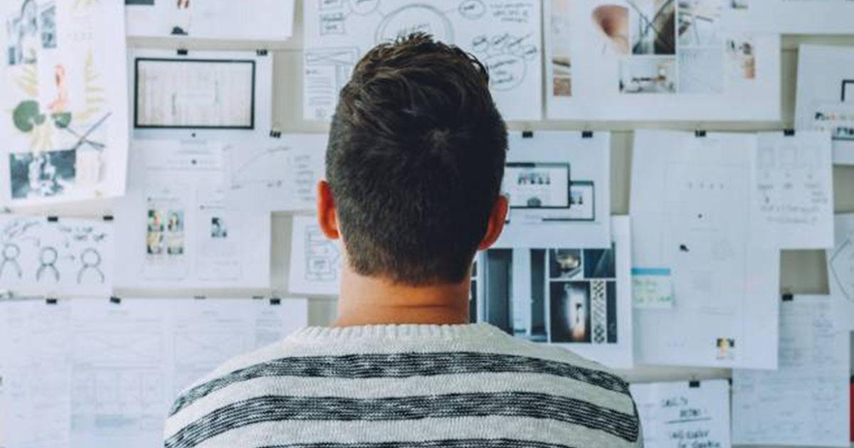 Foto de um homem de costas, olhando para um quadro cheio de papeis, representando os mitos sobre empreendedorismo