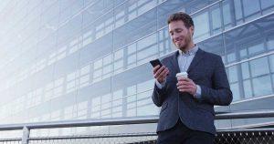 Foto de um homem em pé tomando café e mexendo no celular representando o mobile marketing