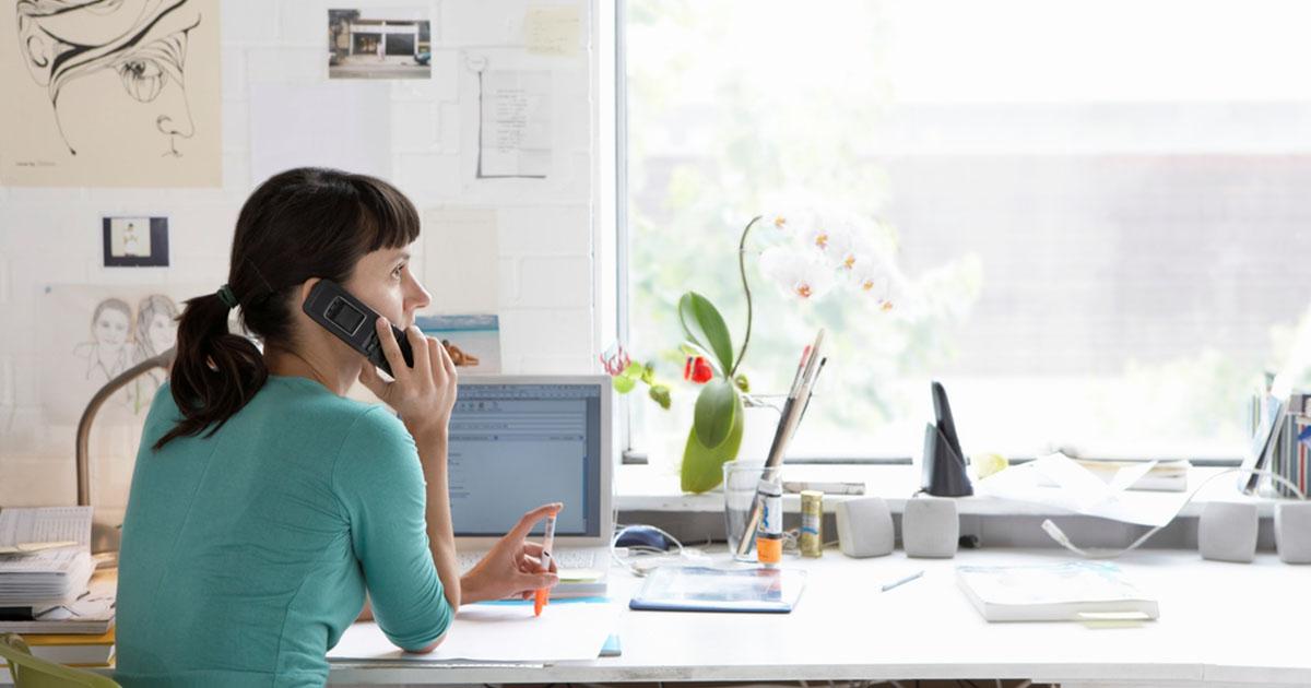 Foto de uma mulher trabalhando de casa e falando ao telefone, representando as novas regras para MEI