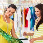 Foto de uma vendedora apresentando um vestido para uma cliente, representando o perfil de clientes