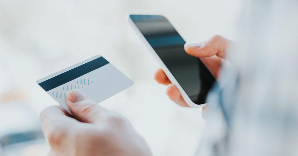 Foto de um homem com um cartão na mão e um celular na outra, representando a plataforma digital Yubb
