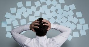 Foto de um rapaz com as mãos na cabeça, representando a ansiedade no trabalho