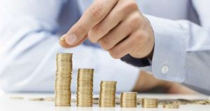 Foto de um homem contando moedas representando os cursos de finanças