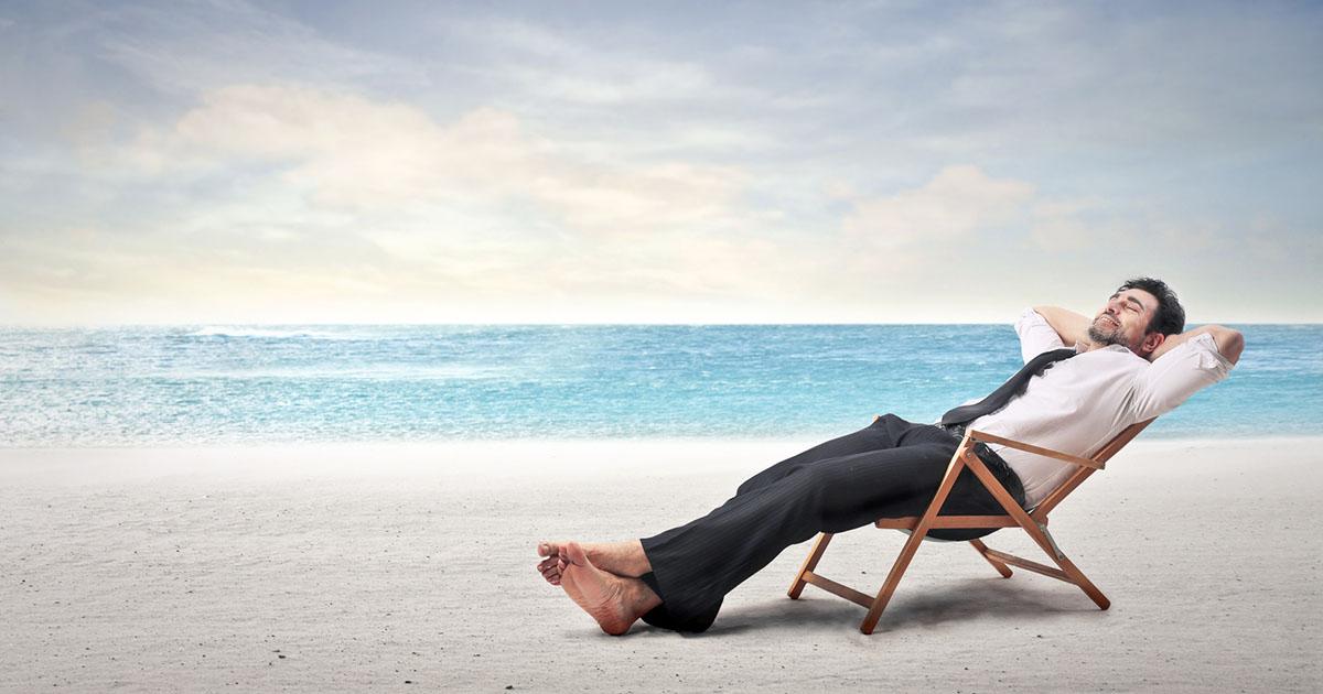 Foto de um homem vestido de camisa e calça social, sentado à praia, representando as férias coletivas