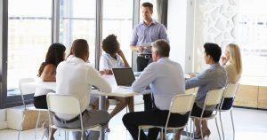 Foto de uma equipe reunida em uma mesa, representando a gestão da equipe de vendas