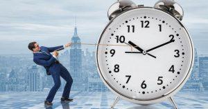 Foto de um homem segurando um relógio, representando os hábitos improdutivos