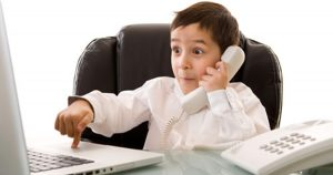 Foto de um menino falando ao telefone e mexendo em um notebook, representando as lições de crianças