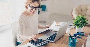 Foto de uma mulher trabalhando de casa e fazendo contas, representando a NFA-e