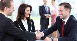 Foto de três pessoas conversando e sorrindo, dois homens e uma mulher, representando a postura profissional no ambiente de trabalho
