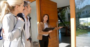 Foto de um casal visitando uma casa com a corretora, representando como abrir uma imobiliária