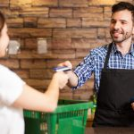 Foto de uma mulher pagando à um atendente com cartão, representando como abrir uma mercearia