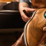 Foto de um homem arrumando um sapato, representando como abrir uma sapataria