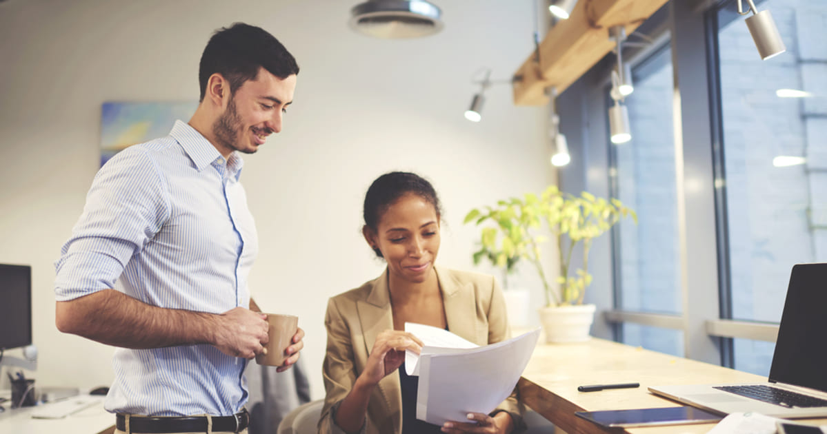 Foto de um homem e uma mulher conversando, representando o papel do contador para abrir empresa
