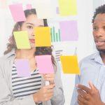 Foto de duas pessoas vendo alguns postits, representando o design thinking na gestão de pessoas