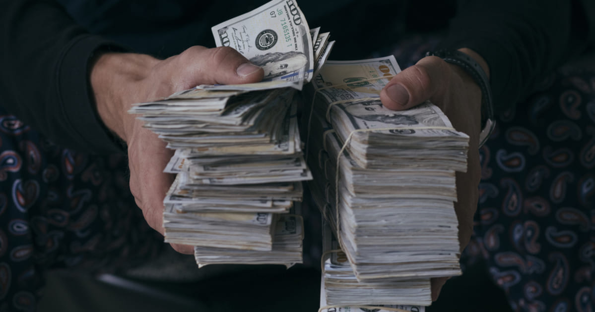 Foto de um homem segurando dois amontoados de dinheiro, representando os hábitos dos milionários