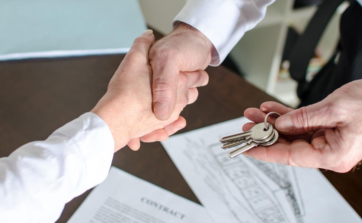 Foto de duas pessoas se cumprimentando, representando os passos para abrir uma imobiliária